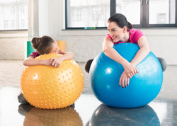 Happy Mother And Daughter Lying On Fitness Balls And Smiling Each Other.jpg