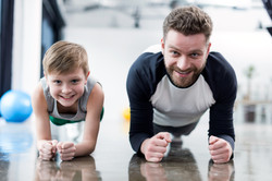 Man And Boy Doing Plank Exercise At Fitness Center.jpg