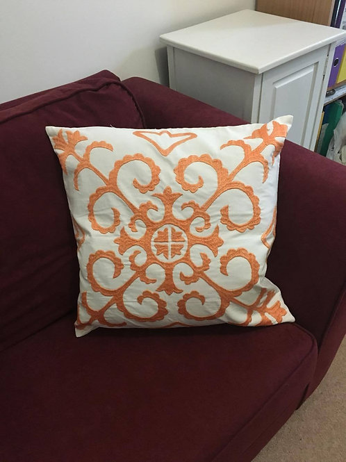 White cushion cover with orange embroidery