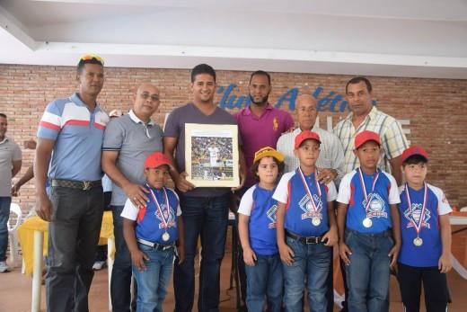 Chaguito Olivo acompañado por el lanzador Juan Grullón, Nardo Fernández y otros miembros de la Liga, premia a parte de los niños más destacados.
