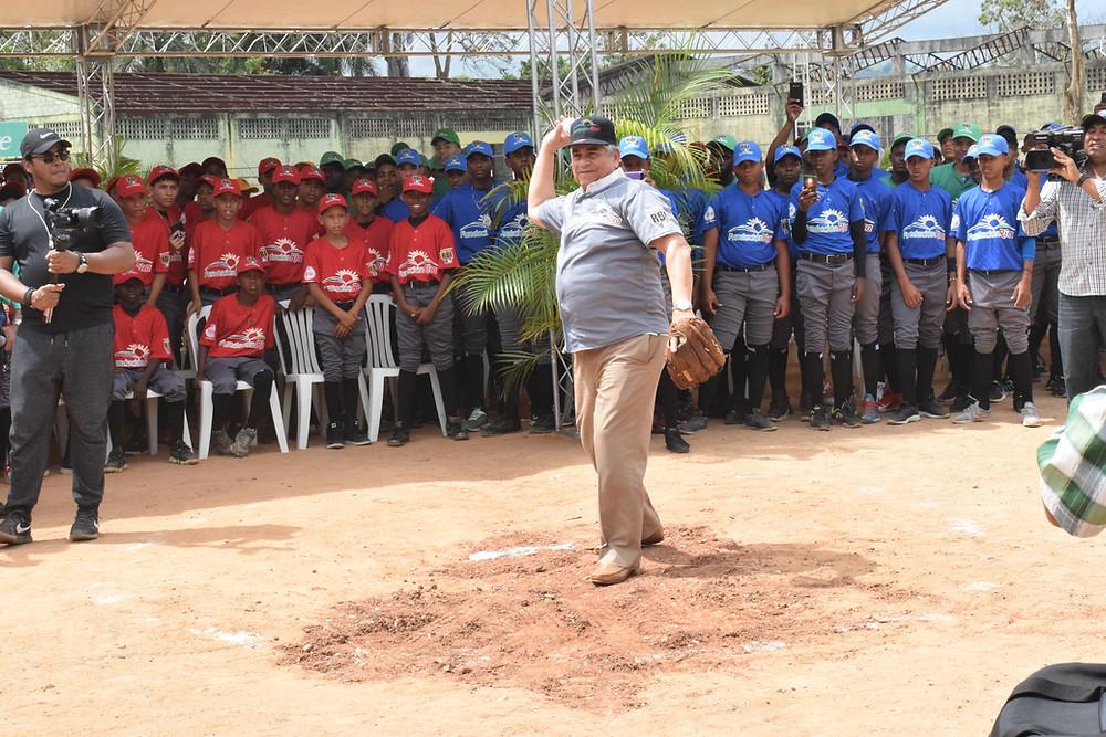 Winston –Chilote- Llenas al realizar el lanzamiento de honor en la inauguración del Torneo RBI Fundación Rica de Villa Altagracia, con parte de los equipos al fondo.