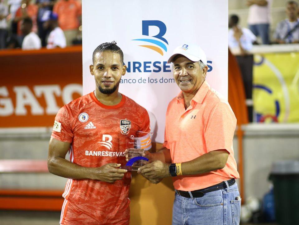 Rafa Flores es premiado por Pedro Genaro Pérez como el Jugador Banreservas del Cibao FC.
