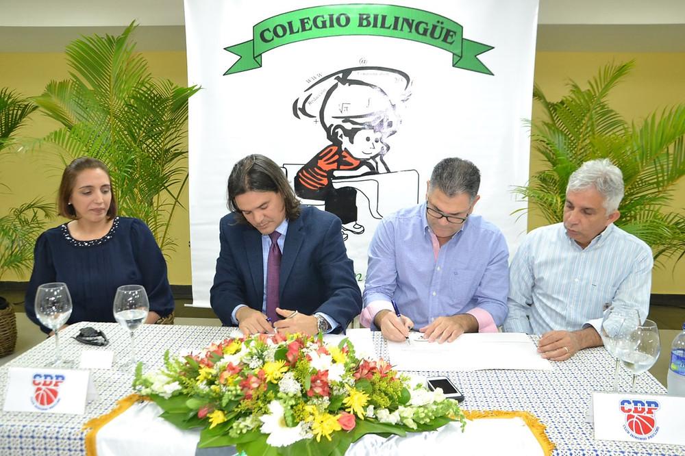 Fauntly Garrido por el New Horizons y Joselito Ureña firman el acuerdo, para la escuela de baloncesto y observan como testigos Irka Taveras y Jorge Luis Ceballos.