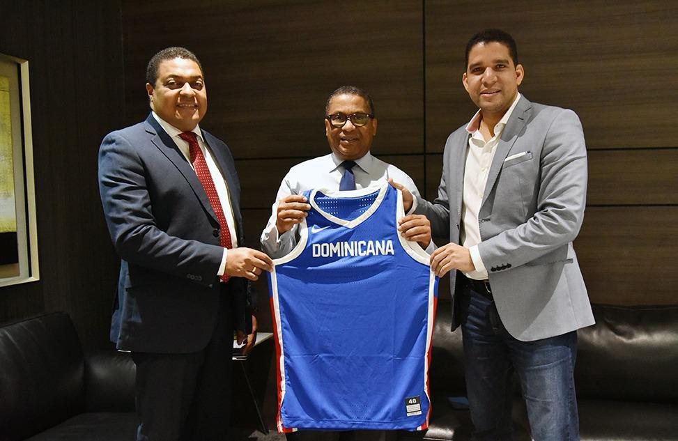 El ingeniero Ramón Pepín, ministro de Obras Públicas, recibe la camiseta de la selección nacional dominicana de baloncesto de parte de José Monegro y Rafael Uribe