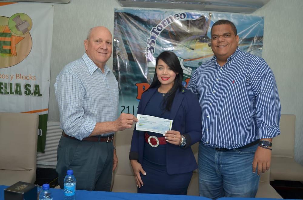 Awilda Guzmán entrega un aporte a nombre de Coopsano a Víctor Estrella y Julio Peña para el Torneo de Pesca al Pez Vela.