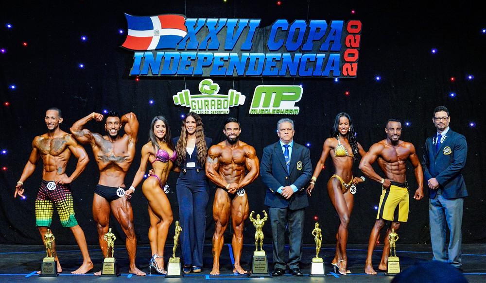 Los señores, Tony Peña R, presidente de la Federación Dominicana de Fisiculturismo y Fitness; el tesorero de la misma, Eddy Pilier y la campeona nacional, Haidy Cruz, entregan los premios a los ganadores absolutos