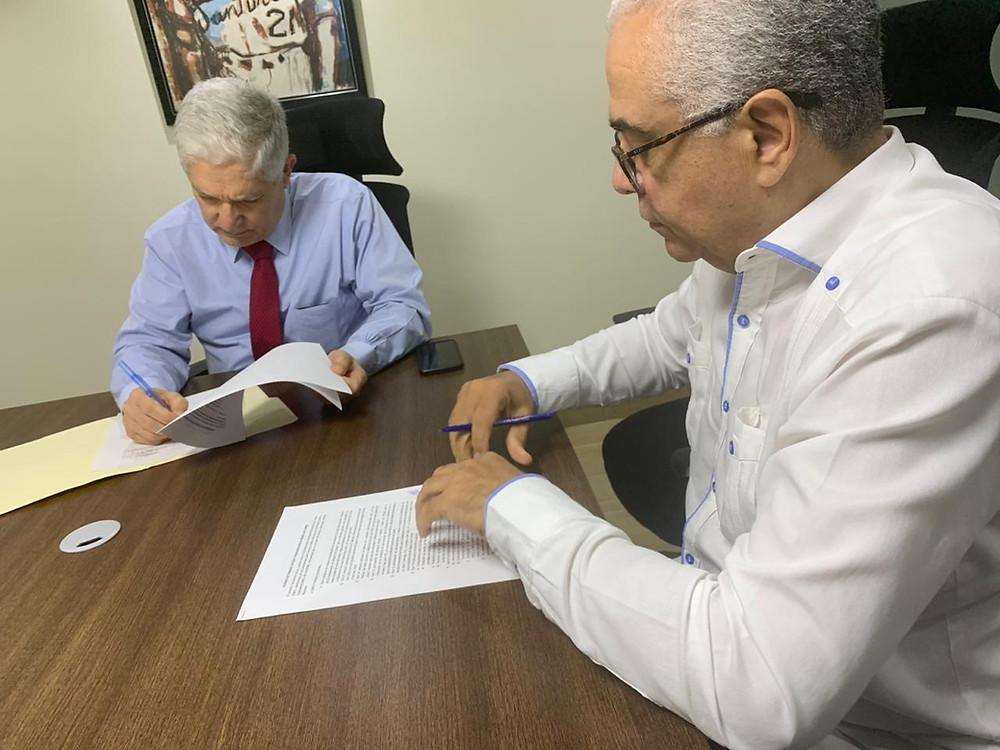 Juan Francisco Puello Herrera y Alfredo Martínez firman el acuerdo para la difusión de capsulas de la Serie del Caribe.