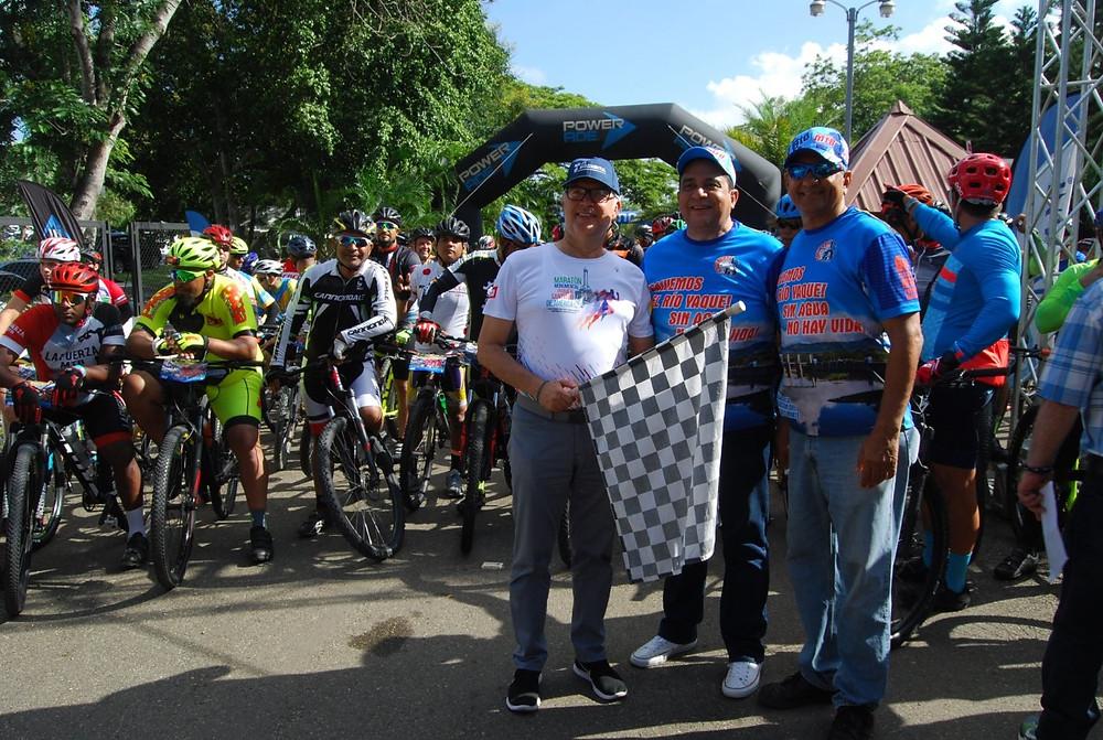 Henry Tavárez acompañado por el ingeniero Rafael Solano y el licenciado José Miguel Minier, de Cocinorte realiza el banderazo de salida.
