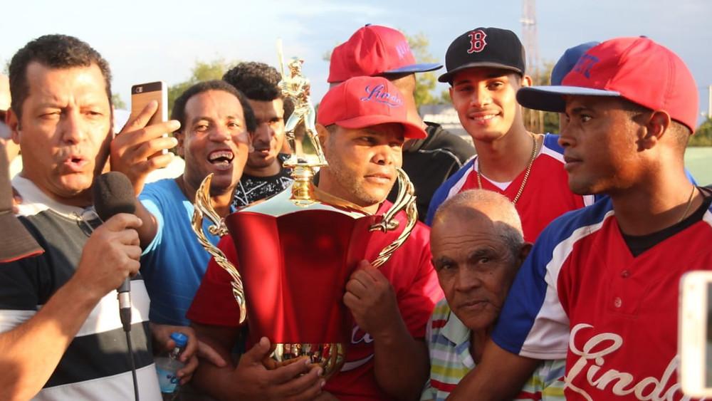 El presidente de la ABOS Diógenes (Tite) Núñez entrega la Copa Banca Deportiva Sánchez Sport a Geraldo Jiménez manager campeón del equipo de Navarrete.