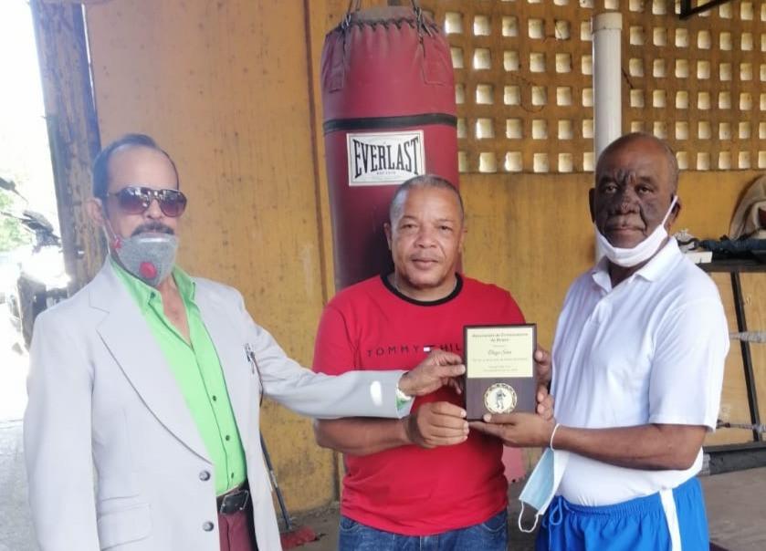 Rafael Jaquez y Chencho Peña entregando la placa a Diego Sosa