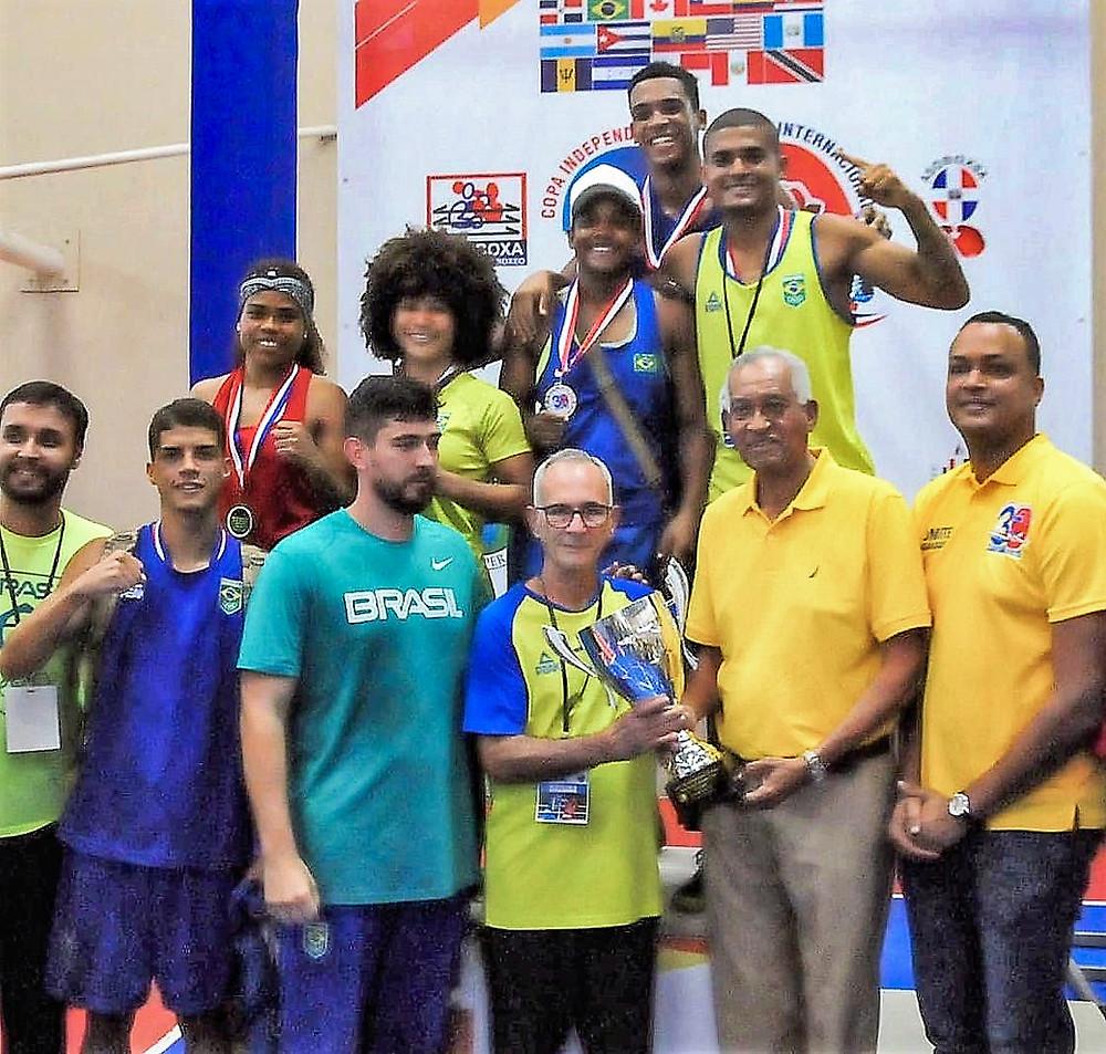 Los señores, Radhamés Espinal, presidente del Comité Organizador, de la XXXIX Copa Independencia de Boxeo y Bienvenido Solano, gloria de ese deporte, entregan el galardón de primer lugar a la selección de Brasil