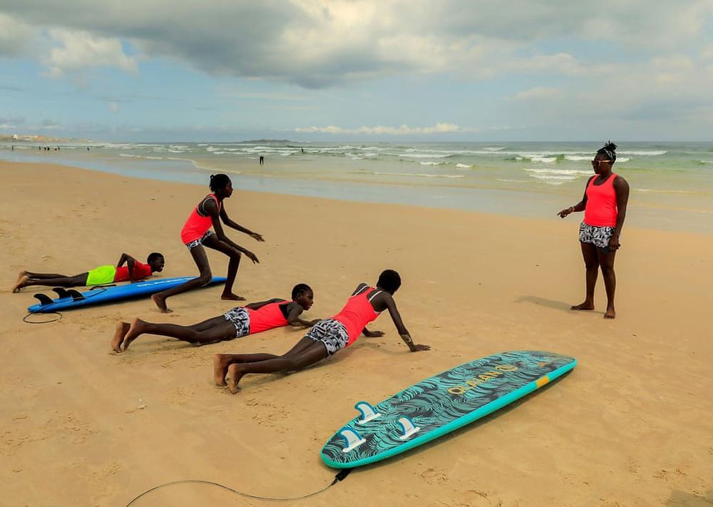 A surfista Khadjou Sambe ensinando surfistas iniciantes em Dakar.