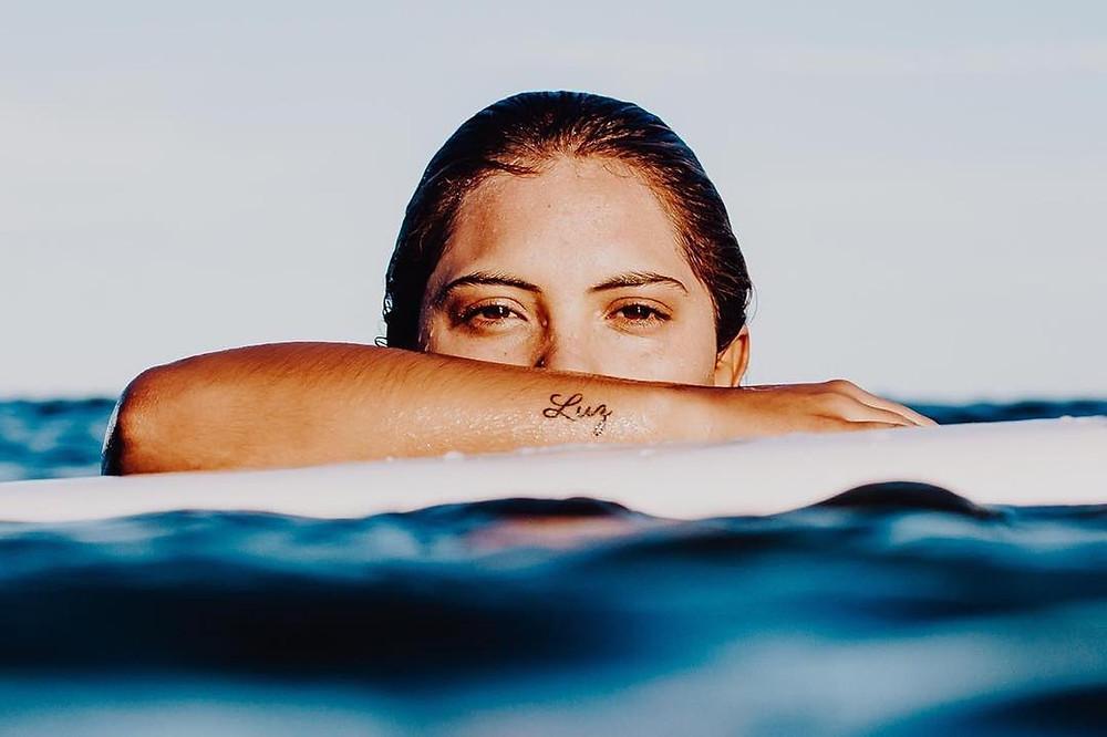 """A surfista Tainá Hinckel na água mostrando sua tatuagem com a palavra """"Luz"""""""