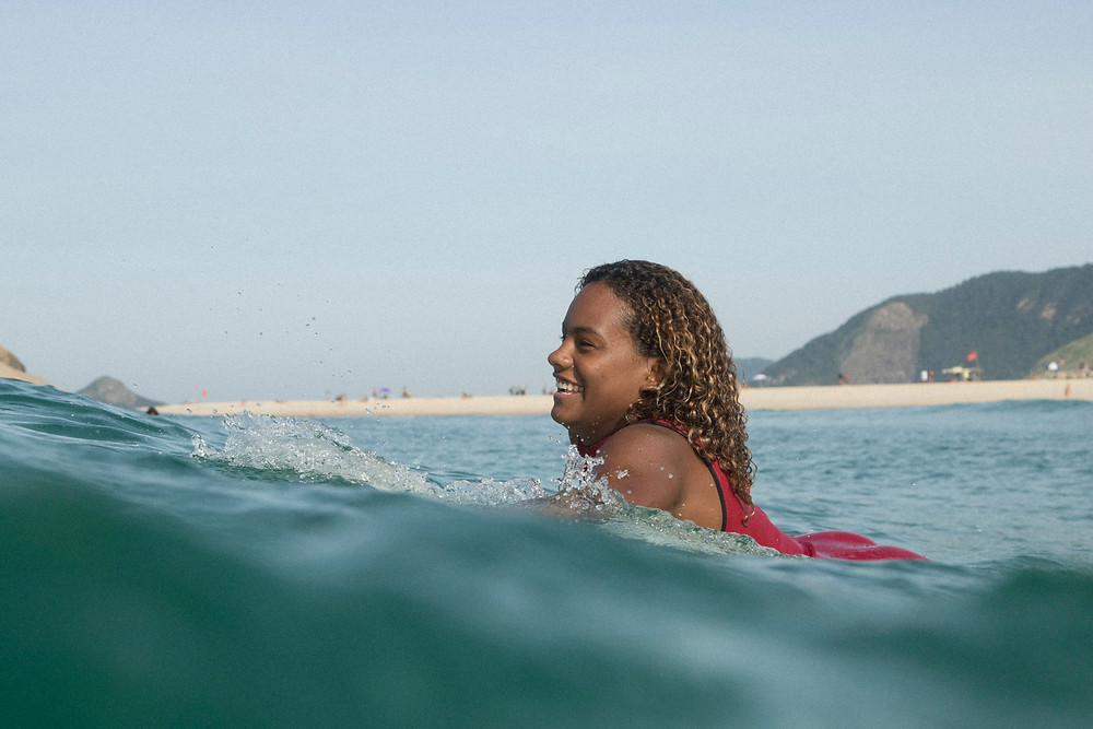 A surfista Yanca Costa no mar sorrindo