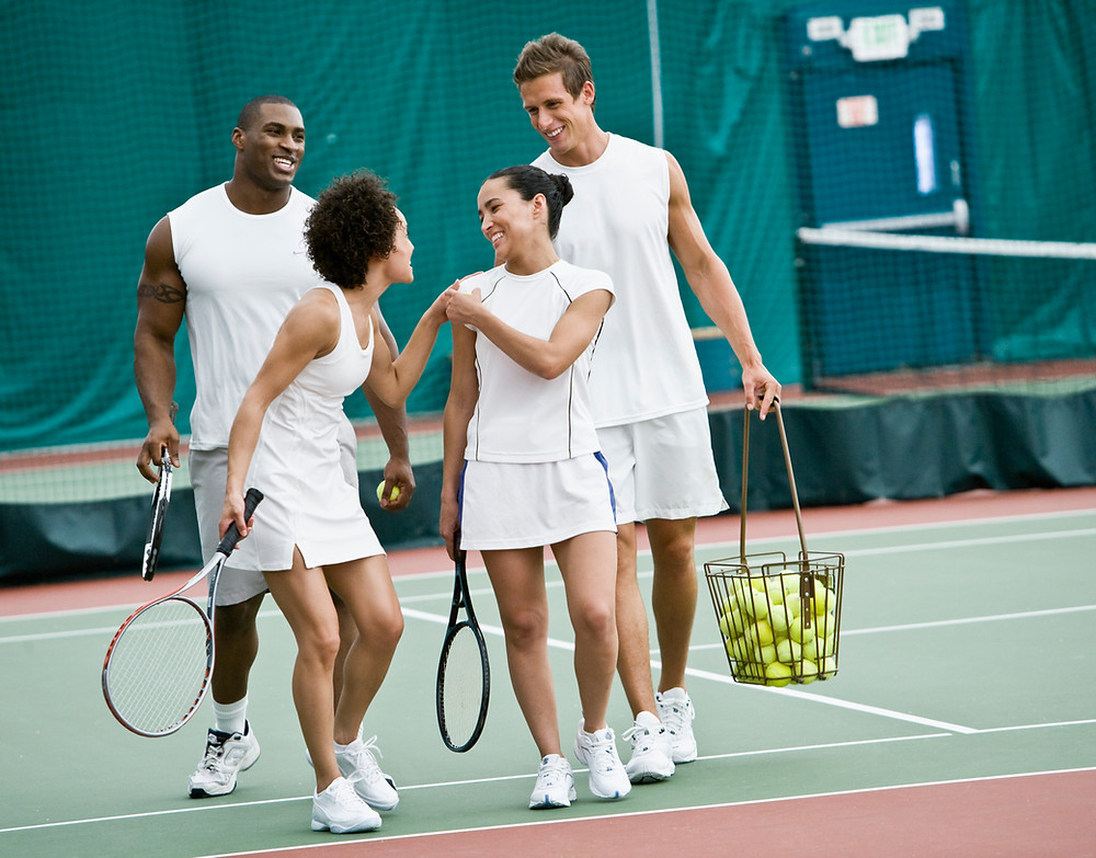 A group of four people in white tennis clothes smile at one another while carrying tennis equipment on a tennis court
