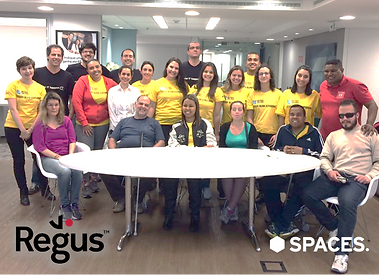 #pracegover: foto tirada ao final com todos os participantes do projeto ao redor da mesa no escritório da Regus, de pé 15 pessoas, a maioria vestindo camisetas amarelas, sentados os 6 deficientes visuais