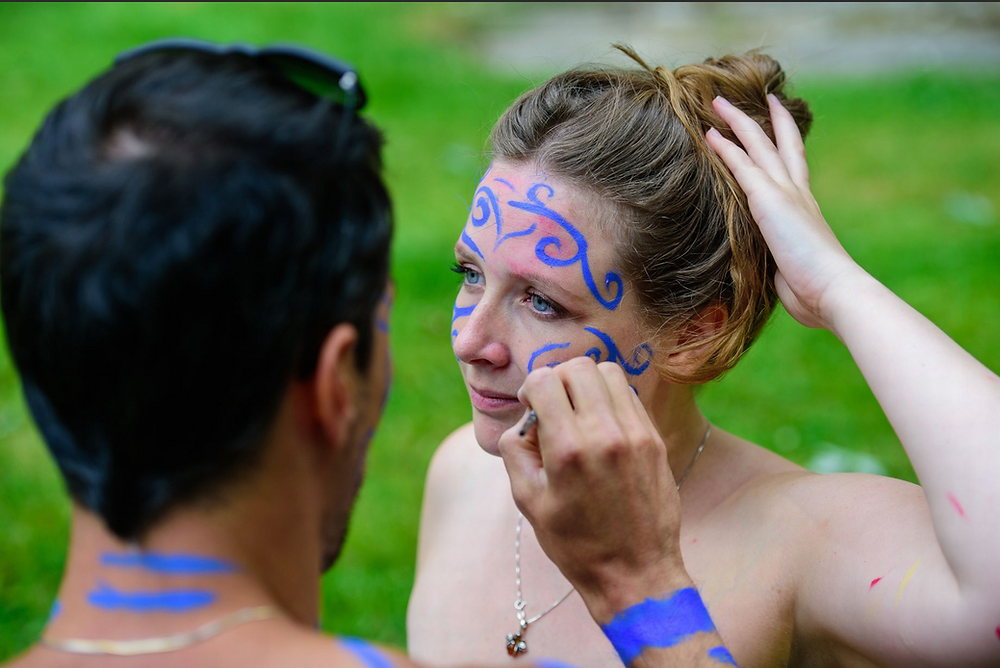 Man painting blue swirls on womans face