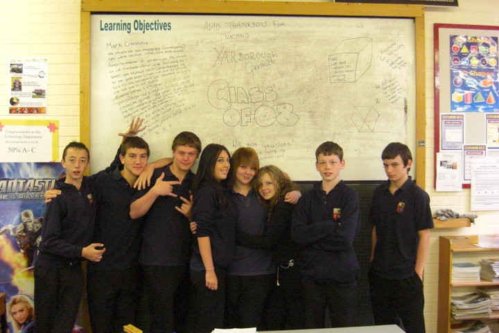 5 boys and three girls stood in front of a whiteboard in a school classroom. Class of 08 written on the board.