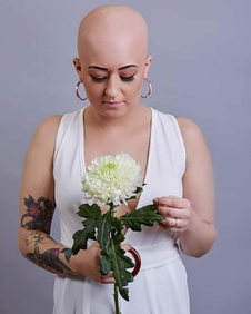 Photo of Amy bald staring at flower