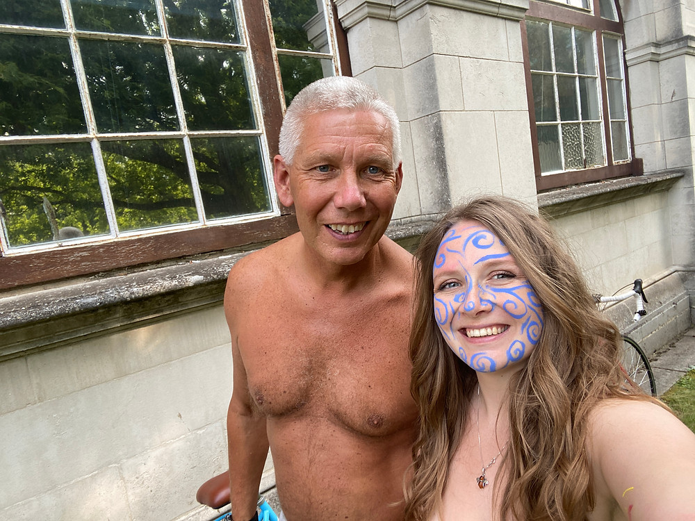 Tanned man stood with woman with face painted blue