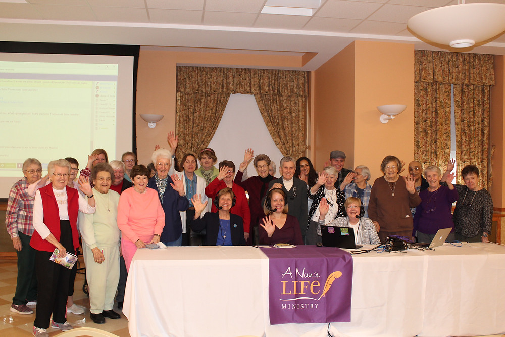Sisters, Associates, and local community members who were in the audience wave to those who are tuning in online