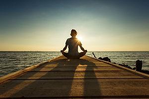 joyful-man-meditating-on-pontoon-over-a-