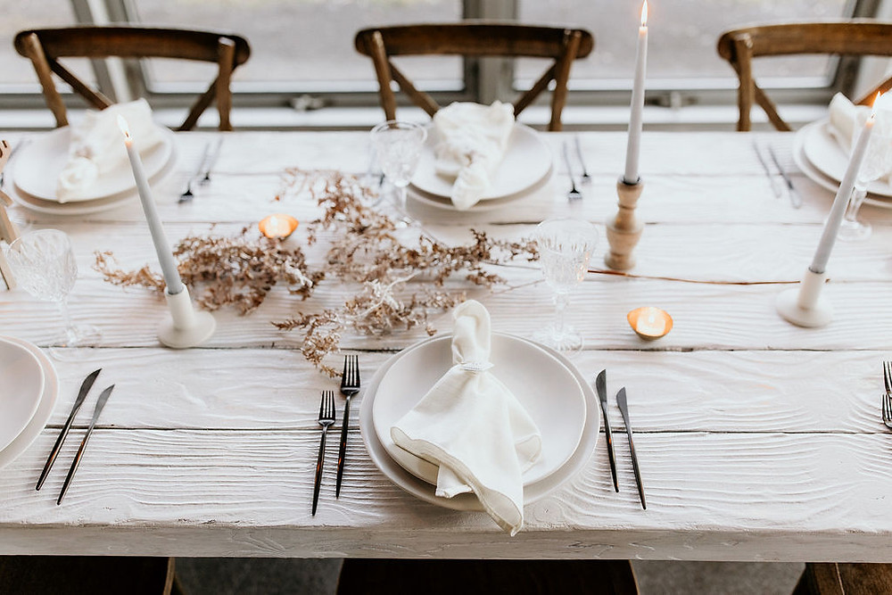 Décoration de table de mariage hivernal bohème et nordique. orte-bougie moderne en porcelaine blanche, porte-bougie pépite d'or, lampion bol en métal doré, couverts zen noirs, sous-assiettes et assiettes lichen blanc naturel, coupes en cristal vintage, serviette de table effet lin ivoire. Photo par Cathy Lessard, fleurs par Elodie Fleuriste, design par La vie est une fête.