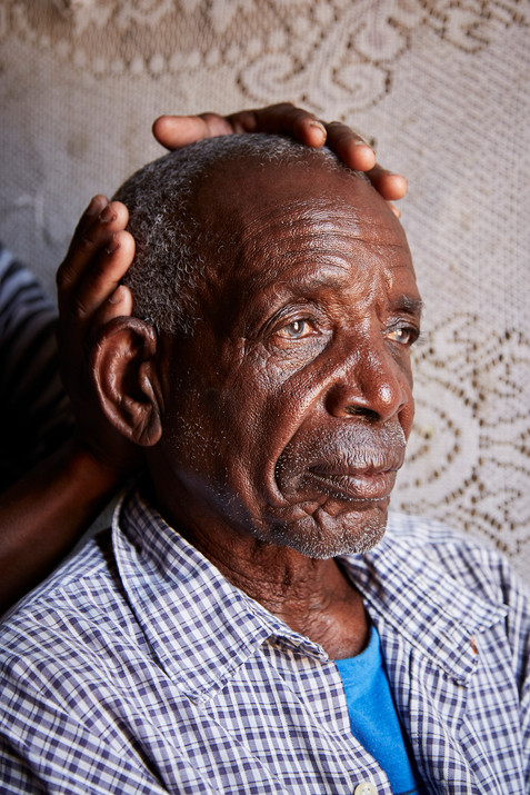 Titus Ihemba (73) is lovingly attended to by his daughter on a rare visit back to his family and village. 7 October 2020.