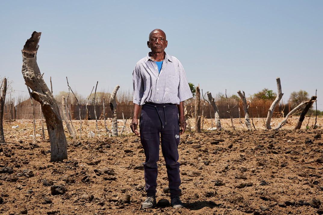 Titus Ihemba (73), in an empty kraal (a holding pen for cattle) in Sizongoro Village, Rundu. An African families wealth is measured in livestock and often makes up the fines levied by witchdoctors. Ihemba was fined 85 cattle by the witch doctor for 4 unexplained deaths within the community which effectively left him bankrupt. 13 October 2020.