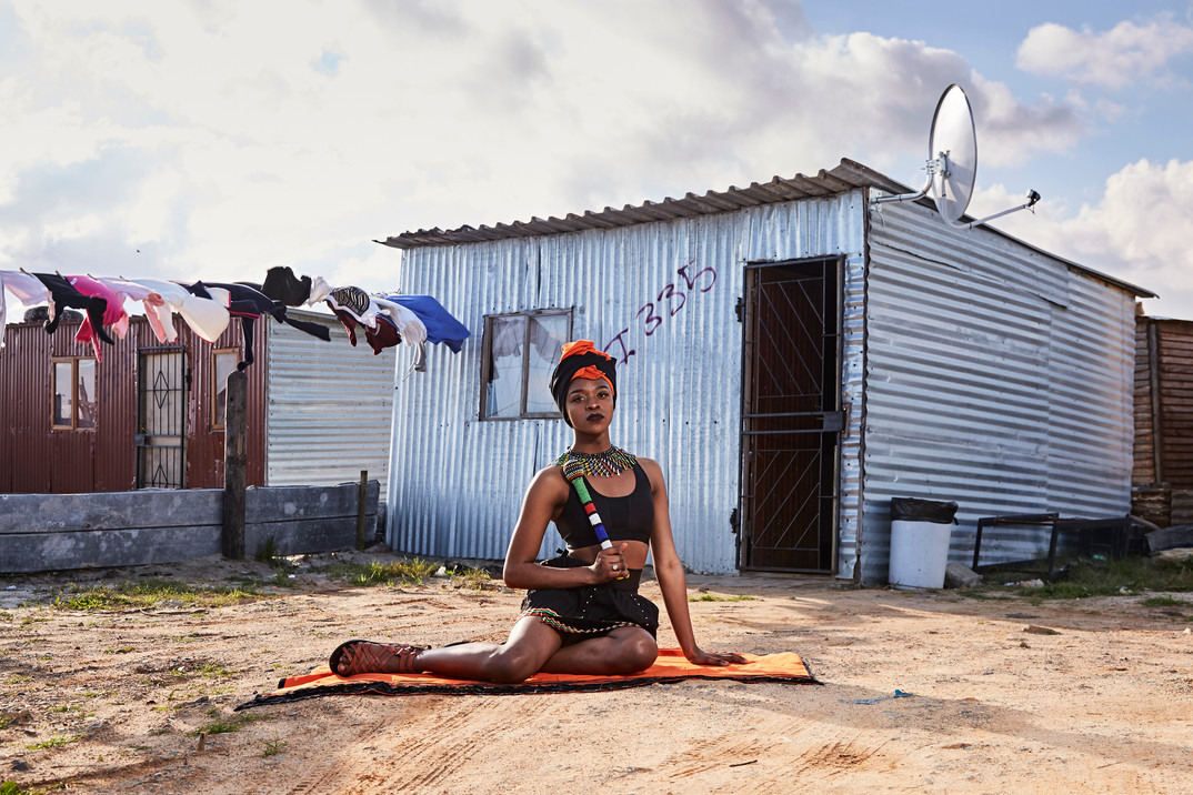 "Mthulic Vee Vuma (Thuli), a trans woman from Lingelihle township in Malmesbury, is pictured in front of a shack in Khayelitsha dressed in traditional female Xhosa clothing. This is done to challenge binary thinking that strongly differentiates between masculine and feminine traditional clothing. ""Here we use our own culture to frame our identity, even though this contests the societal norms and gendered dress codes that are set in our culture. We frame our identity by tying together our stories of subjectivity and culture,"" Vuma says. Her family initially struggled to accept her as a trans woman, believing it was a curse, but she says they now give her total support. Aug. 4, 2019."