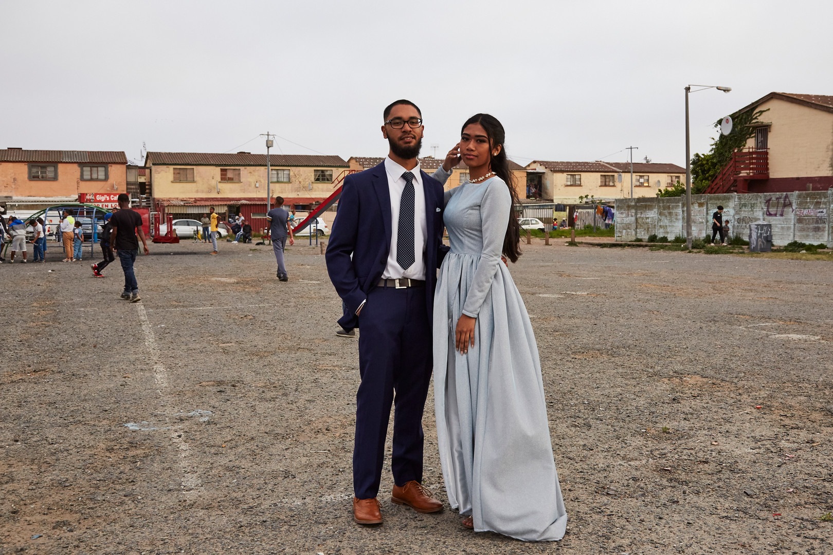 """Shakeelah Davids (19) who attended Wynberg High School poses with her date Daniel Laun in Parkwood where she grew up, in a dress made by a family friend. She is the eldest of 3 siblings and the second to finish high school, after her mom. In 2020 she wants to study interior design and she aspires to create a better life for herself and her family.   """"The youth need to find inspiration and aspiration. Most people in my community don't aspire to anything more than what they see every day. They should aspire to greater things and want more for themselves and their families."""" 27 Sep. 2019"""