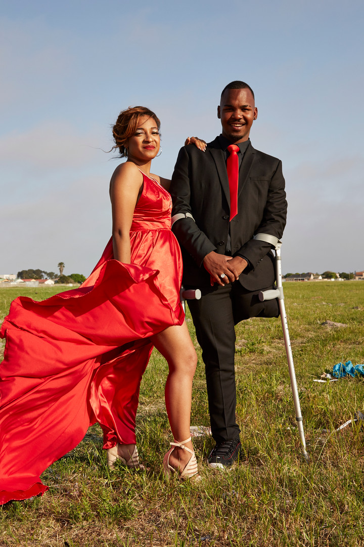 """Chad Johnson (19) and his date Jaylin Arendse in Lotus River where they celebrated Chad's achievement at his aunt's house before going to the matric dance. Chad wants to work for the South African police force in an admin position. """"I want to work in my own community so that I can make a difference and help people."""" Chad has faced many adversities in life. He was born with one leg and his father passed away when he was 16. Coming from an area where just getting to school can be a challenge due to gang violence Chad had to find the strength within to persevere. """"I dropped out of school for a month after my father passed away. I realized that I am the eldest and that my mother was all alone. I wanted to make my father proud so I decided to go back to school. This was a very challenging time for me."""" 27 Sep. 2019"""