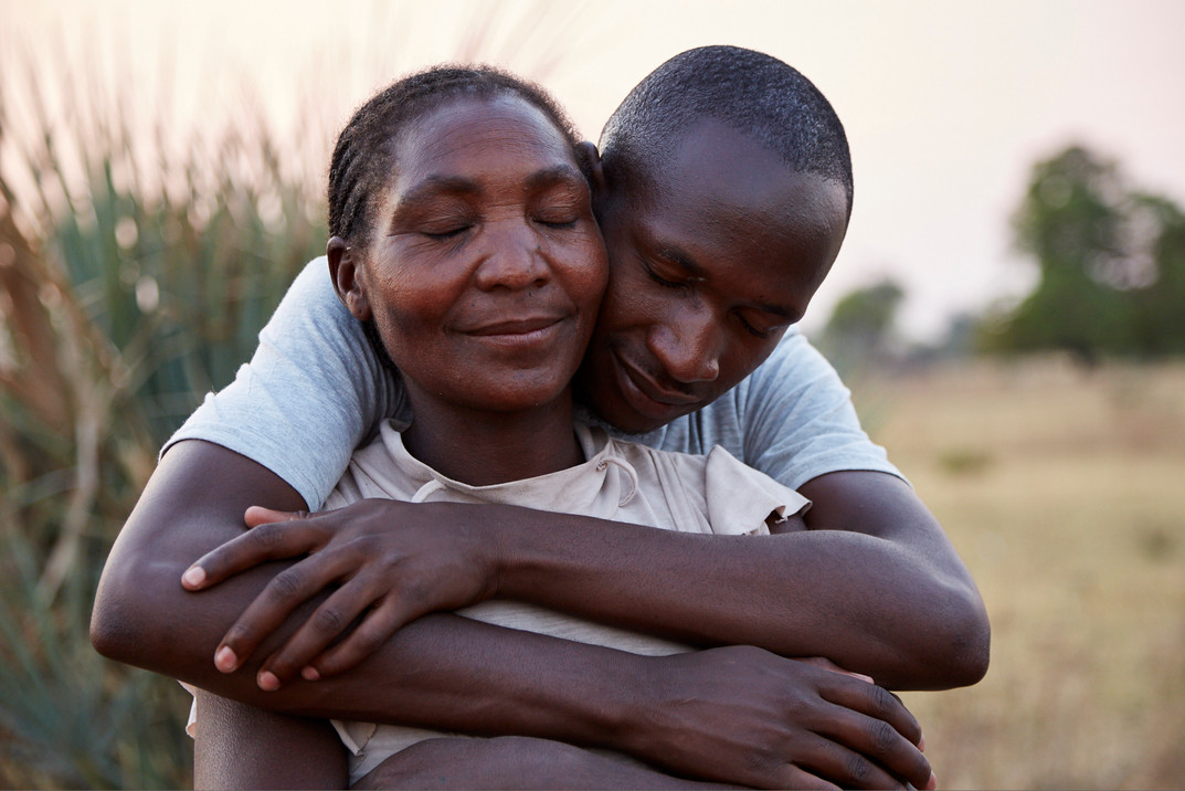 Andreas Haingura (23) tenderly holds his mother Frankhilde Katumbu Haingura (48) outside the family home in Siya, Rundu. Andreas a high school student at the time of the attack on his mother, remained alone in the family village for 6 years after Haingura fled following the attempt on her life. Having completed his schooling Andreas has enrolled at the University of Namibia to study nursing and dementia care. Unlike many of the Namibian youth, Andreas is not a believer in witchcraft and is actively involved in community education about dementia. 8 October 2020