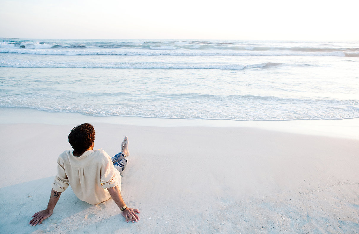 A man sits at on a beach gazing at the ocean