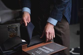 Man selecting custom suiting fabric