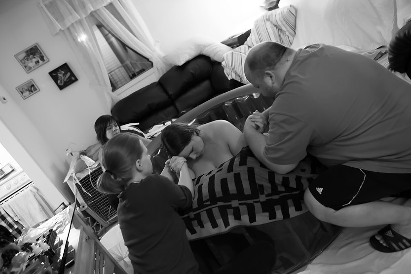 Doulas & Midwives working togethe at home water birth