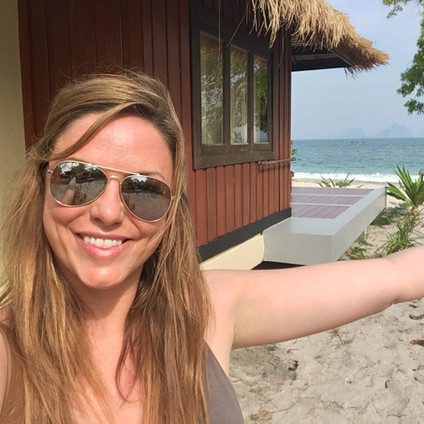 Travel Queen Owner Mel at the tip of Koh Mook Sivalai Resort's private beach peninsula, with one of the beachfront villas in the background. Travel Queen
