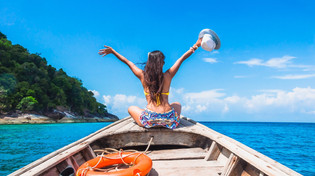 Woman enjoying Thailand on longtail boat