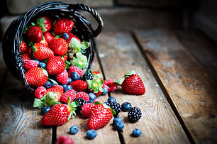 Mix of fresh berries in a basket on rust
