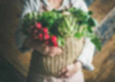 Female farmer in linen apron holding bas