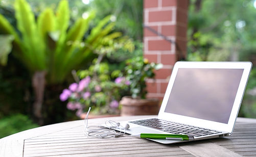 Laptop with ear phones and green pen, on