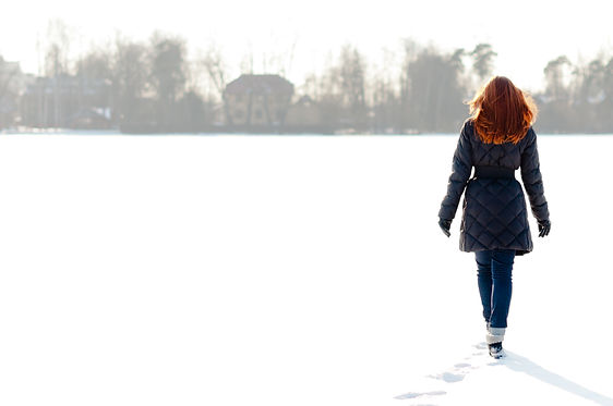 Pretty red haired girl walking on frozen lake and making footpath (1).jpg