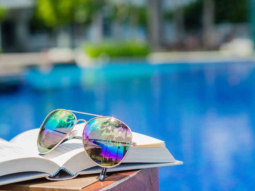 sunglasses on open book at the side of s