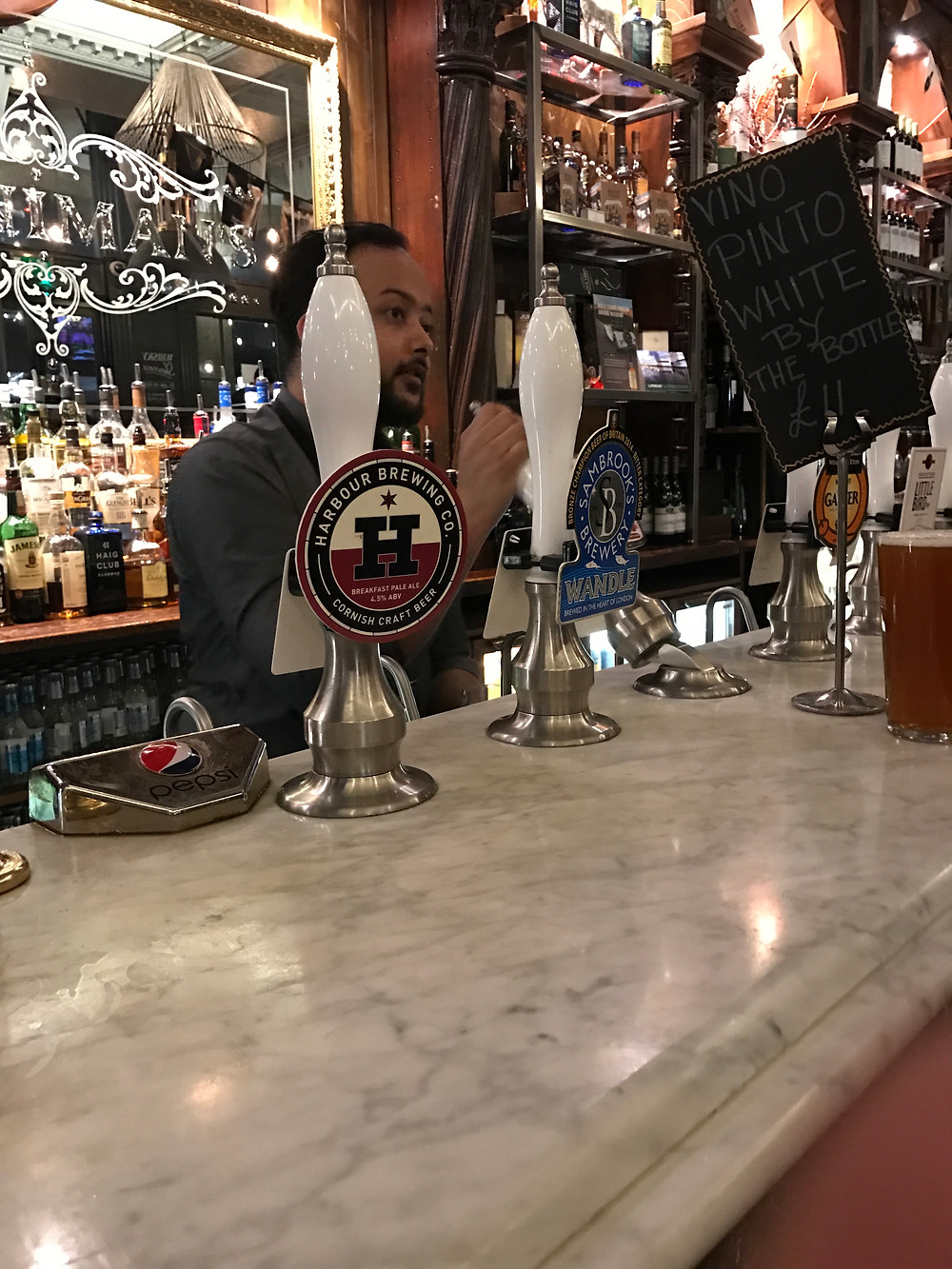 Bartender pumpking ale from a cask at a pub in the heart of London