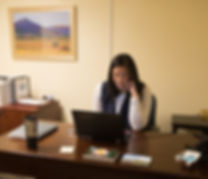 A woman sits at a desk with a laptop in an office.