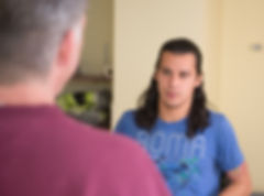 A man talks to another man in a counseling session.