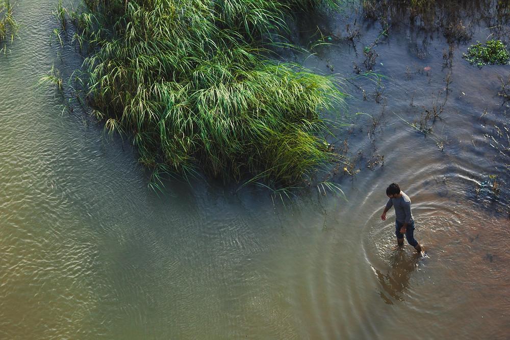 Mies kävelee matalassa ruskean värisessä vedessä suoraan ylhäältä otetussa kuvassa.