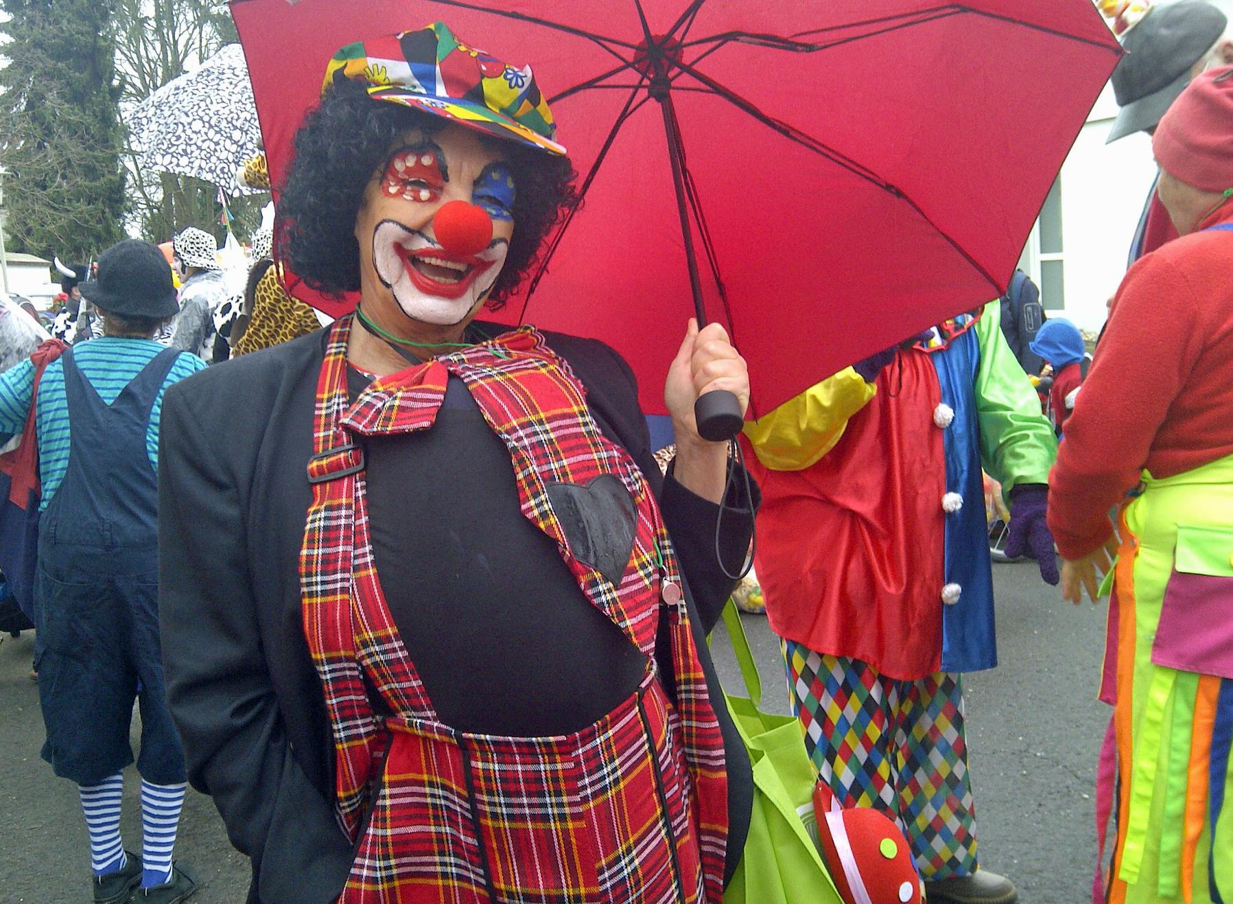 Schöner Clown mit rotem Schirm
