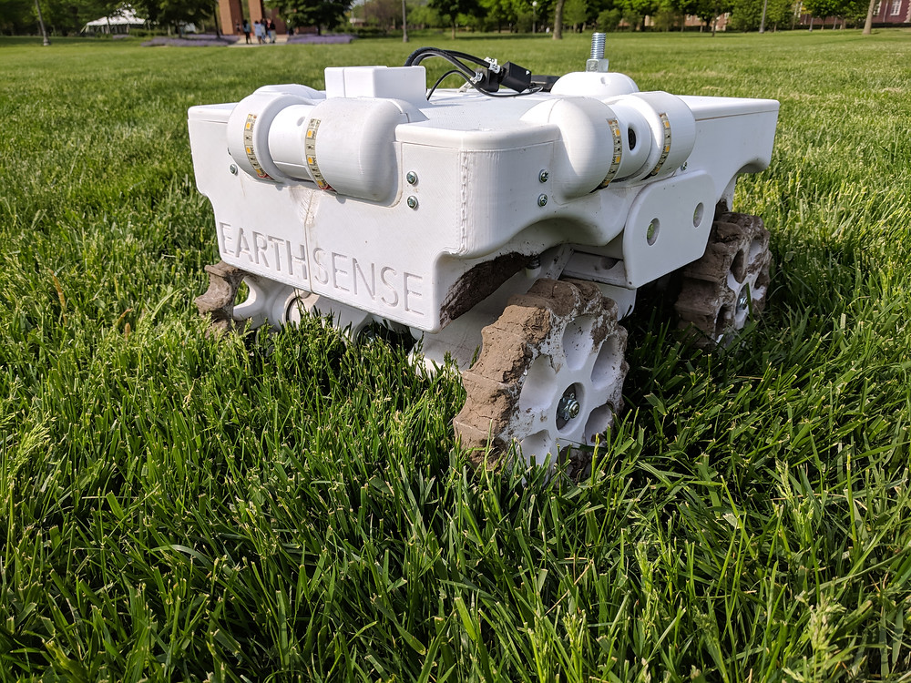 White, square TerraSentia robot sits on a grassy lawn.
