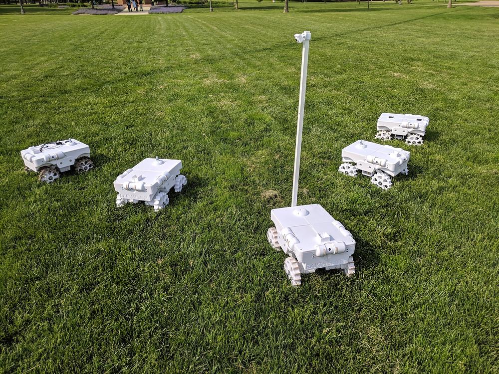 Five white TerraSentia robots sit on a lawn.